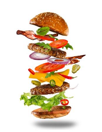 Big burger maison savoureux avec des ingrédients volants sur fond blanc. Banque d'images - 74052604