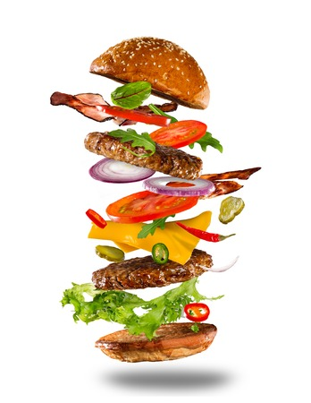 Big tasty home made burger with flying ingredients on white background.