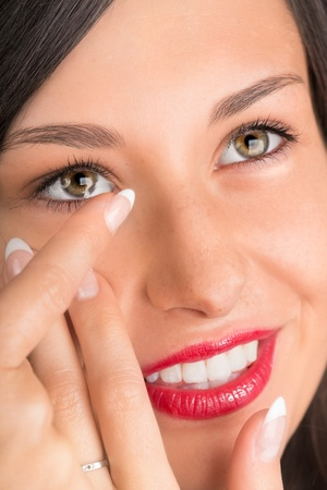 wearer: Young woman putting contact lens in her eye.