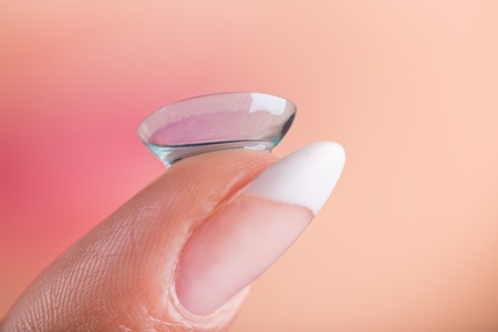 Young woman with contact lens on her finger. Macro shot. Stock Photo