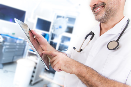 Doctor with stethoscope and tablet in a hospital, close-up. Stock Photo