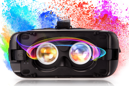 VR virtual reality glasses with colored powder isolated on white background. Stock Photo