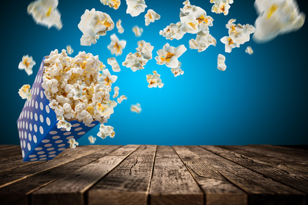 Popcorn explosie op oude houten tafel, close-up.