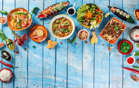 Verschillende Aziatische maaltijden op rustieke achtergrond, bovenaanzicht, plaats voor tekst. Aziatisch voedselconcept. Stockfoto