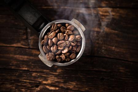 hot temper: Granos de café fresco en cafetera.