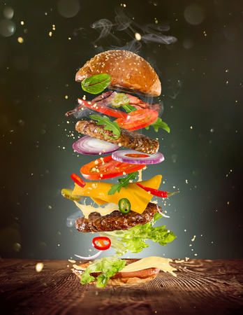 Big tasty burger with flying ingredients.