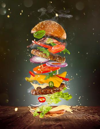 Gran hamburguesa sabrosa con ingredientes voladores. Foto de archivo - 76824669