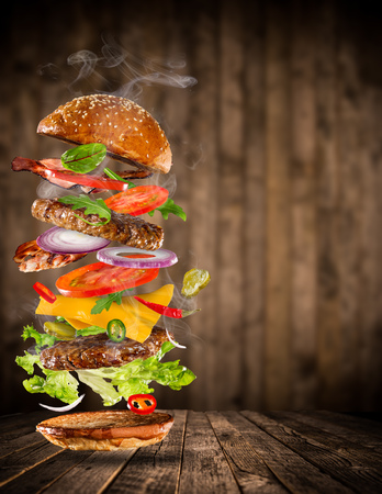 Big tasty home made burger with flying ingredients. Stock Photo