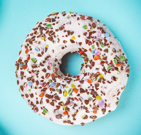 Glazed donut with colorful sprinkles on blue pastel background.