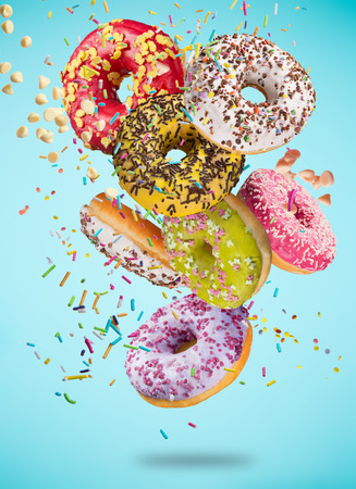 Tasty doughnuts in motion falling on pastel blue background, close-up. Stock Photo