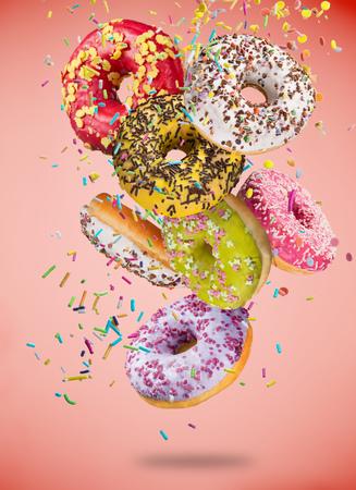 Lekkere donuts in beweging die op pastel blauwe achtergrond vallen.
