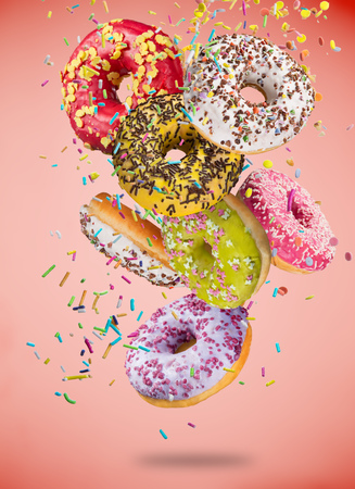 Tasty doughnuts in motion falling on pastel blue background.