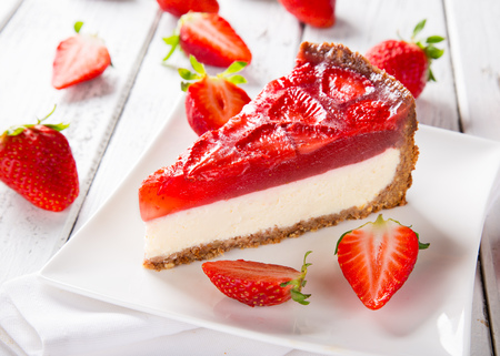 Delicious cheesecake with strawberries on wooden table.