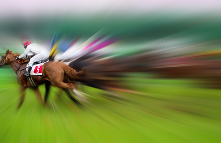 Race horses with jockeys on the home straight. Blurred motion effect.