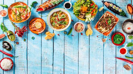 Verschillende Aziatische maaltijden op rustieke achtergrond, bovenaanzicht, plaats voor tekst.