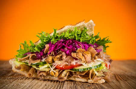 Close up of kebab sandwich on old wooden table. Фото со стока