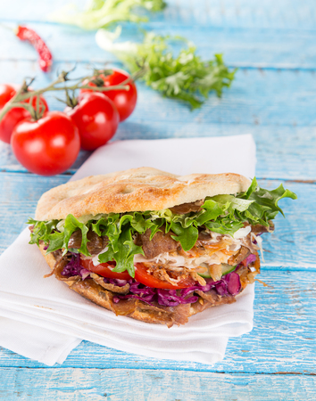 Close up of kebab sandwich on old wooden table. Stock Photo