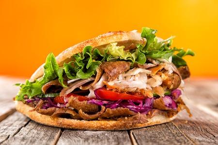 Close-up van kebab sandwich op oude houten tafel.