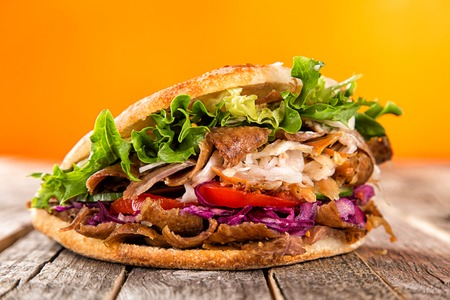Close up of kebab sandwich on old wooden table. Archivio Fotografico