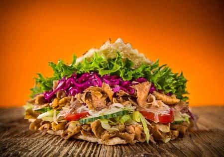 Primo piano di panino kebab sul vecchio tavolo di legno Archivio Fotografico - 81200487