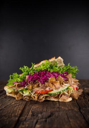 古い木製のテーブルのケバブ サンドイッチのクローズ アップ。