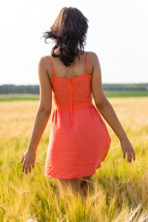 Meisje dat in rode kleding op tarwegebied loopt. Oogstthema. Stockfoto