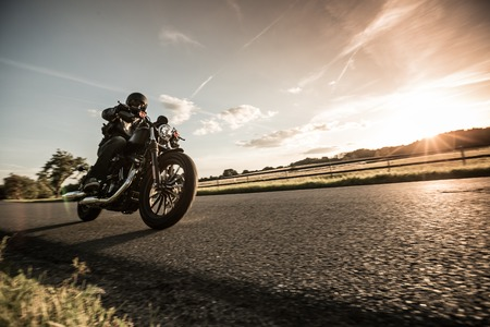 Man riding sportster motorcycle during sunset. 免版税图像