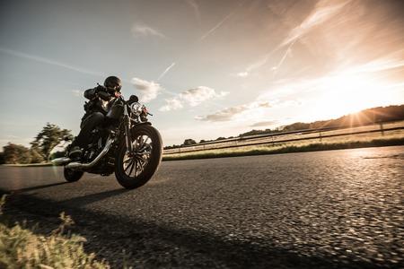 Man rijden sportster motor tijdens zonsondergang.