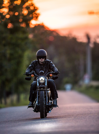 Man riding sportster motorcycle during sunset. Фото со стока