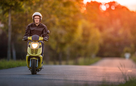 road bike: Man riding scooter during sunset. Stock Photo