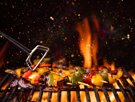 Chicken skewers on the grill with fire flames