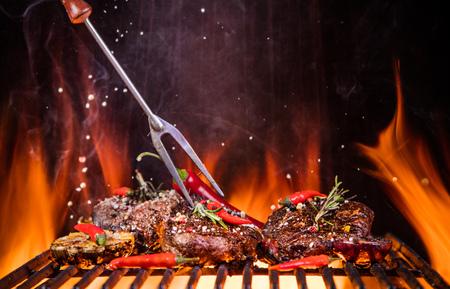 鲜美牛排在烤架上与火火焰