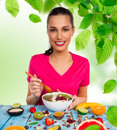 Smoothie bowl with happy young brunette woman. Healthy breakfast. Stock Photo