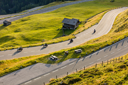 curve road: Motorcycle drivers riding in Alpine highway on famous Hochalpenstrasse, Austria, central Europe. Stock Photo