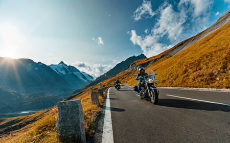 Motorcycle driver riding in Alpine highway on famous Hochalpenstrasse, Austria, central Europe. 版權商用圖片 - 85258688