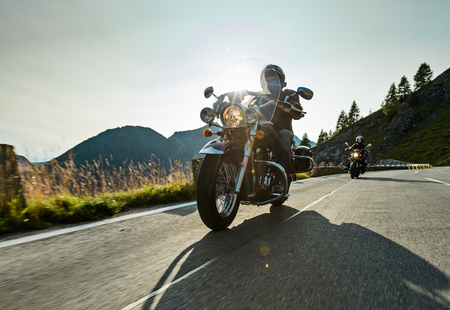 Motorcycle driver riding japanese high power cruiser in Alpine highway on famous Hochalpenstrasse, Austria, central Europe.