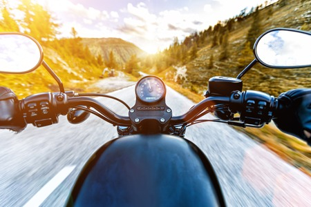 Motorcycle driver riding in Alpine highway, handlebars view, Austria, central Europe. Stock fotó