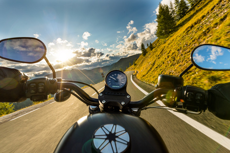 Motorcycle driver riding in Alpine highway, handlebars view, Austria, central Europe. Imagens