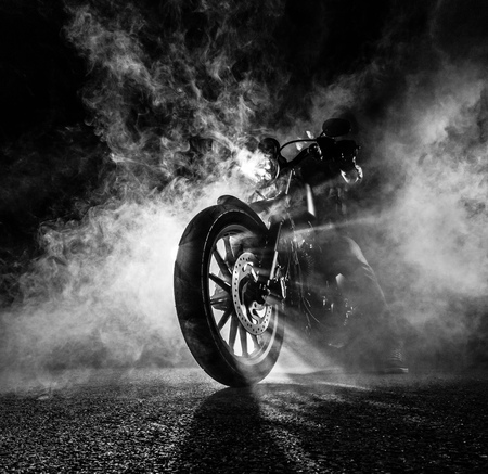 High power motorcycle chopper at night. Smoke effect on dark background.