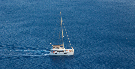 Boat in deep blue water, Santorini, Greece. View from above.