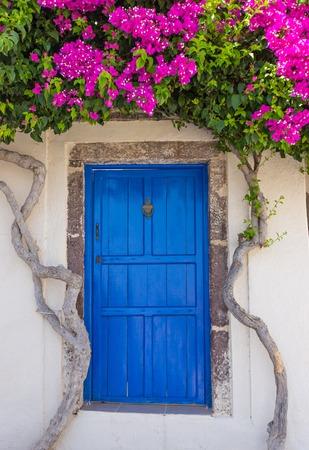 오래 된 마에서 전통적인 오래 된 블루 문 함께 아름 다운 피 bougenvilia 그리스에서 산토리니의 섬에 엠포리오.