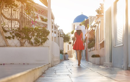 Santorini travel tourist brunette woman in red dress visiting famous white Oia village. Greece, Europe.