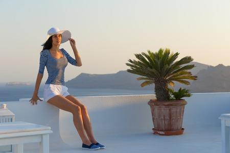 Santorini travel tourist brunette woman visiting famous white Oia village. Greece, Europe.