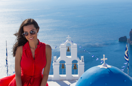 Santorini travel tourist brunette woman in red dress visiting famous white Fira city. Greece, Europe. Stock Photo