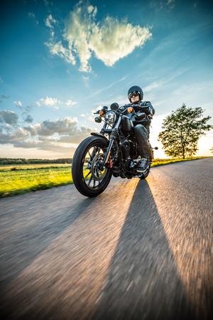 日没時に田舎でスポーツスターのオートバイに乗る男。