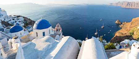 Sunrise view of the blue dome churches of Santorini, Greece, Europe. Фото со стока