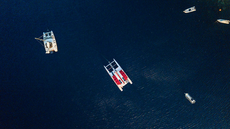 Boats and catamarans in deep blue water, Santorini, Greece. View from above.