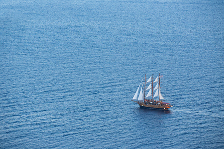 Old wooden boat in deep blue water, Santorini, Greece. View from above.