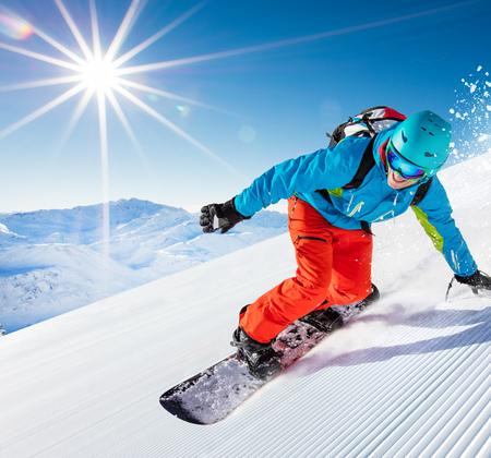 Active man snowboarder riding on slope, snowboarding closeup. Foto de archivo