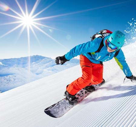 Active man snowboarder riding on slope, snowboarding closeup. Archivio Fotografico